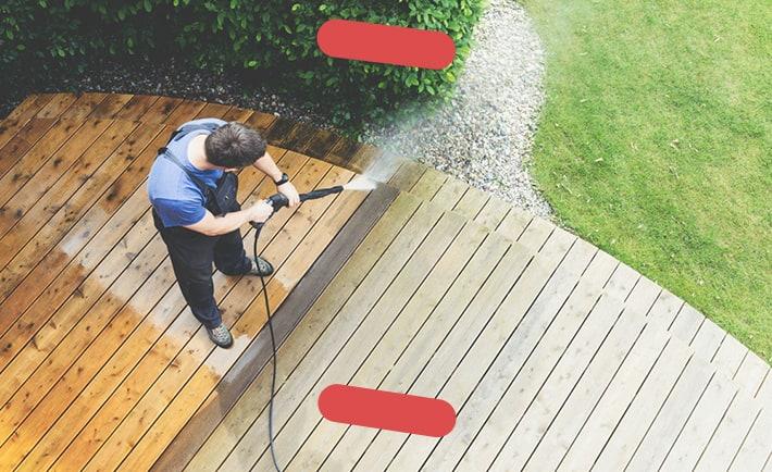Man pressure washing deck