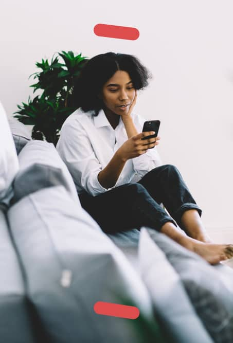 Woman on couch checking smartphone
